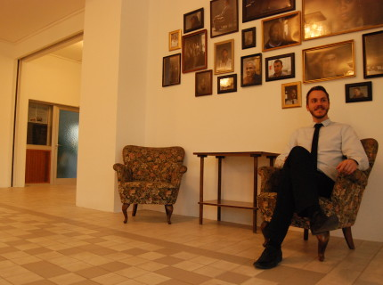 Dutch hotel manager Sebastiaan de Vos knows each of the 20 refugees. Their photos hang on the wall behind him.